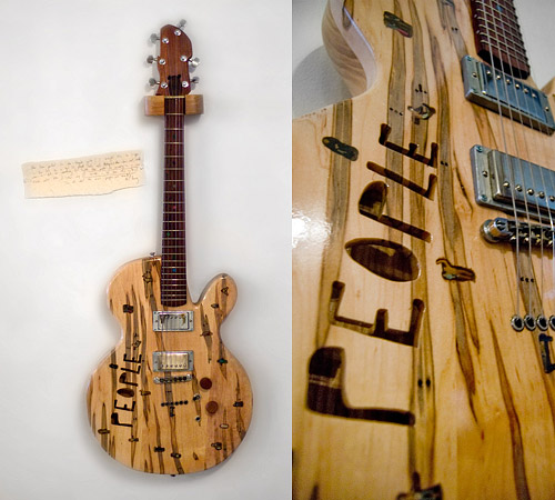Guitar made from wood streaked by the ambrosia beetle as it burrows through maple trees, with a a semi-hollow body and little handpainted figures of people inlaid into the front. The word 'people' cut into the front acts like the 'f holes' on a violin.